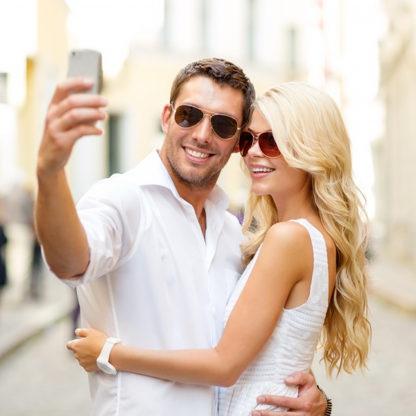 9170568-smiling-couple-taking-selfie-with-smartphone